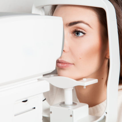 beautiful young brunette lady checks her vision at the clinic. Ophthalmologist. medical, health, ophthalmology concept.